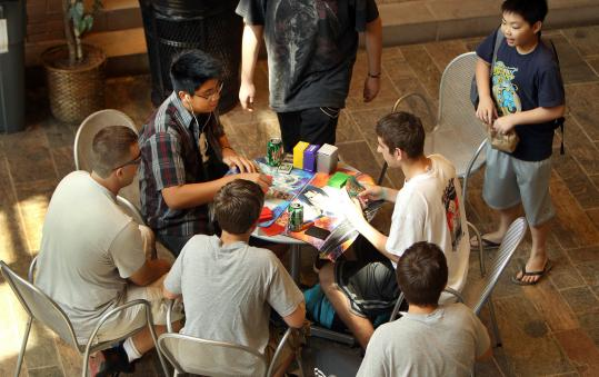 The cafe in the atrium of the Thomas Crane Public Library in Quincy has become a spot for socializing. Here, teens play a card game.
