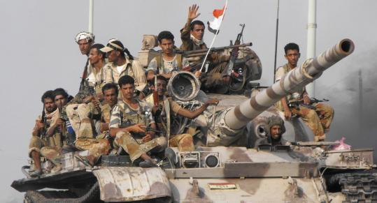 Yemeni soldiers rode through Zinjibar yesterday. Government officials said they reclaimed part of the city from militants.