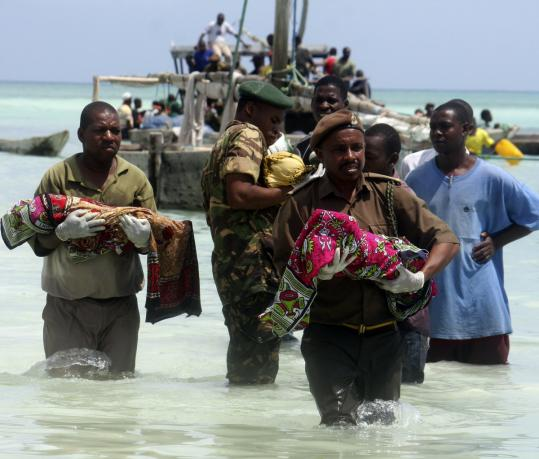 Tanzanian police carried children's bodies from the sea after an apparently overcrowded ferry sank yesterday.