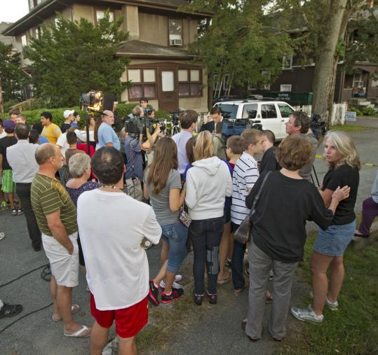 "A crowd gathered yesterday on Harding Avenue, after three men were found slain in an apartment. The Middlesex district attorney said the crime ""does not appear to be a random act.''"