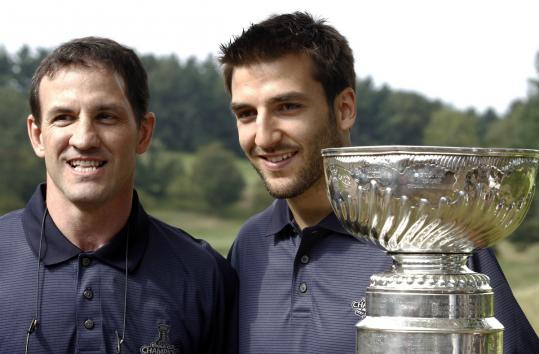 Patrice Bergeron (right) poses with ex-Bruin Normand Leveille next to the Stanley Cup during the team's charity golf tourney.