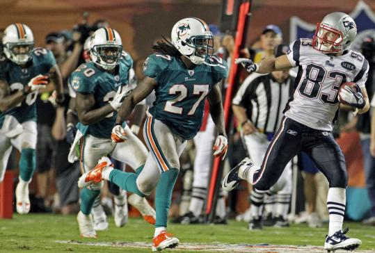 Wes Welker keeps Bennie Sapp (27) and the rest of the Dolphins at bay on his 99-yard touchdown catch.