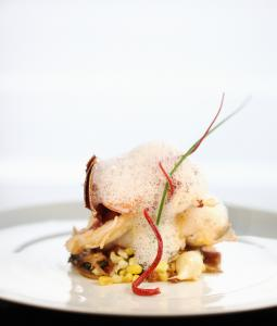 Butterpoached lobster is served out of its shell, with corn, mussels, chorizo, and potatoes.