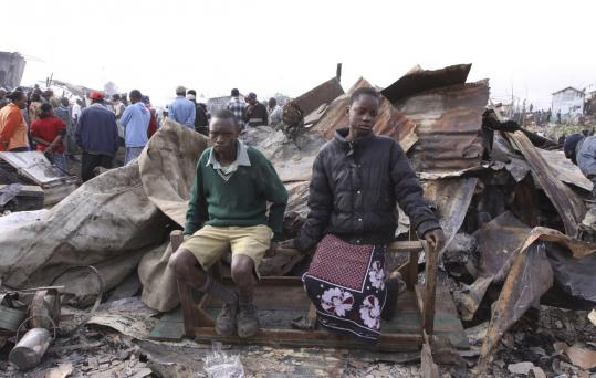 Schoolchildren sat yesterday on the remains of their home, razed by the gasoline pipeline explosion in Nairobi.