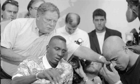 Dave Gavitt, then the Celtics' executive vice president, comforted guard Dee Brown (center) and forward Rick Fox during an emotional press conference following the sudden death of team captain Reggie Lewis in 1993.