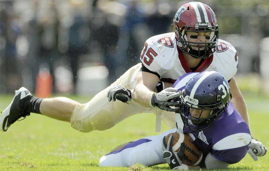 Harvard linebacker Bobby Schneider takes down running back Sam Auffant of Holy Cross.