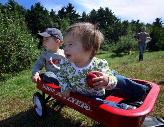 Charlotte and Benjamin Rose of Littleton get a ride to the picking trees at Carver Hill Orchard in Stow.
