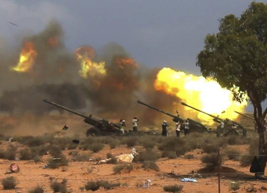 Anti-Khadafy forces fired howitzers east of Surt yesterday. Some officials from Khadafy's regime, as well as one of the ousted dictator's sons, have fled to Niger.