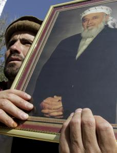A mourner held up a poster of former Afghan President Burhanuddin Rabbani, who died in a suicide bomb attack.