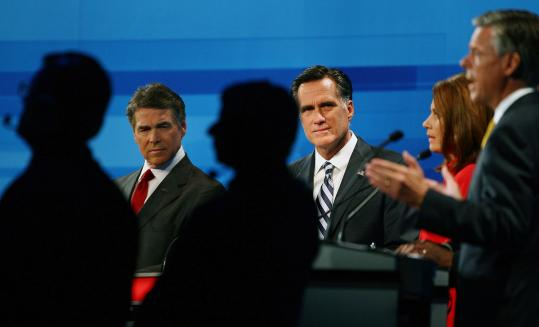 Rick Perry and Mitt Romney, with Michele Bachmann and Jon Huntsman at right, sparred last night over Social Security and the Massachusetts health care law, as each of the two front-runners sought to use his opponent's own words against him.