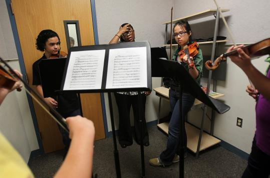 Teacher Mariana Green-Hill (center) led a string class in a small rehearsal space.