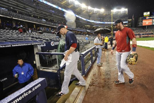 Jon Lester and Jarrod Saltalamacchia leave the field after last night's game was postponed.