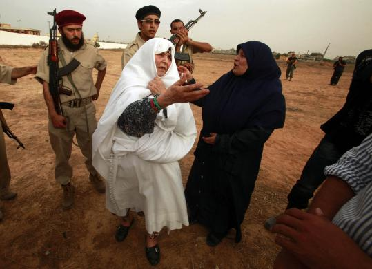 A woman who says her son was killed at Abu Salim prison visited the mass grave site with her daughter yesterday. Excavation has not begun in the desert field.