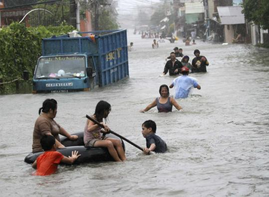 Residents north of Manila struggled yesterday in waist-deep flood waters brought by Typhoon Nesat.