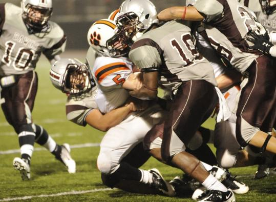 Lynn English players swarm over Beverly's Dom Abate (center) during their game Friday. Beverly trailed early, but came back to win, 36-35.