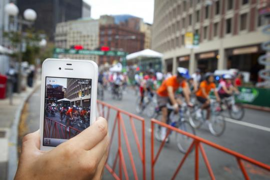 With several major Boston roads closed, Mary Khoshi of Beverly records video of bicyclists near the starting line of Sunday's Hub On Wheels. Her husband, Arash, tackled the 50-mile ride.
