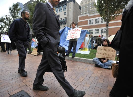 Occupy Boston protesters remained in their tent village in the Financial District yesterday, though their numbers dwindled to about 100 participants. Some say they plan to stay put indefinitely.
