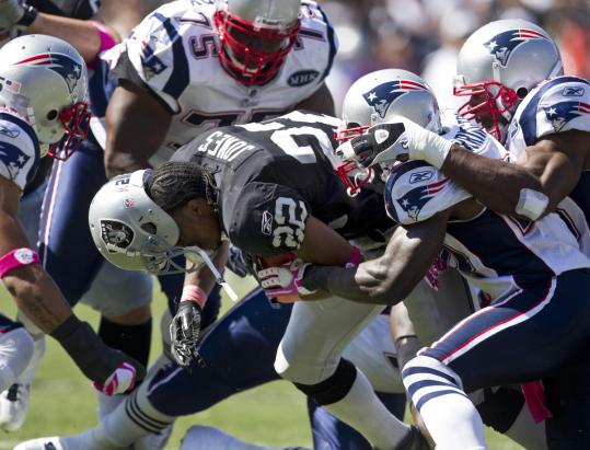 With top tackler Jerod Mayo out, Kyle Arrington and his fellow defenders will have to continue swarming to the ball, as they did on this takedown of the Raiders' Taiwan Jones Sunday.