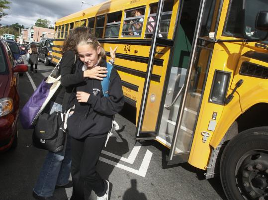 "Megan Wolf - shown greeting her daughter Shaina, 12, at the Jamaica Plain stop yesterday - calls the problem of late-running school buses ""terrible.''"