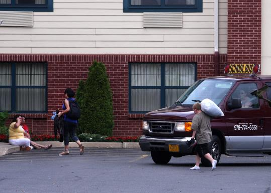 A van drops off a student (with backpack, left) at a hotel at the end of a school day late last month.