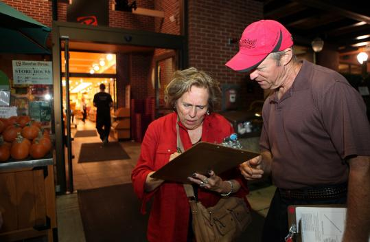 Petitioner Earl Sholley got a signature from Elaine Lapides, a family therapist from Wellesley, outside Roche Bros. in Wellesley.