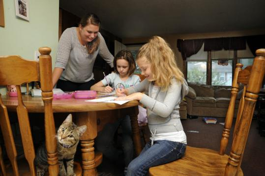 Dracut's Danielle Laferriere works on homework with daughters Kayla and Brooke. The family hopes to buy a house (below) on the same street.