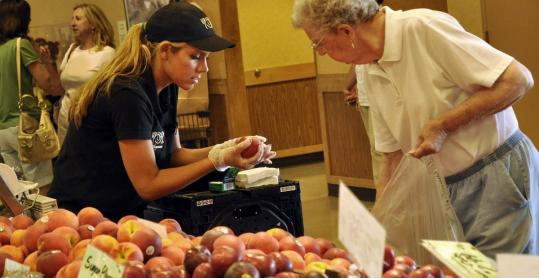 Elizabeth Ognenovski helped Jean Ferris shop for peaches at the Wegmans supermarket in Pittsford, N.Y., in July. The personal touch is a store staple.