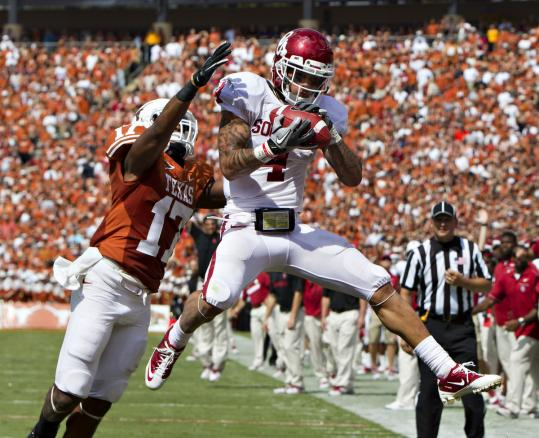 Oklahoma receiver Kenny Stills catches a touchdown pass over Texas defender Adrian Phillips during the Sooners&#8217; win in Dallas.