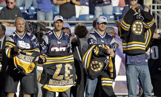 Members of the Bruins remove their hockey sweaters to reveal Patriots' jerseys yesterday.