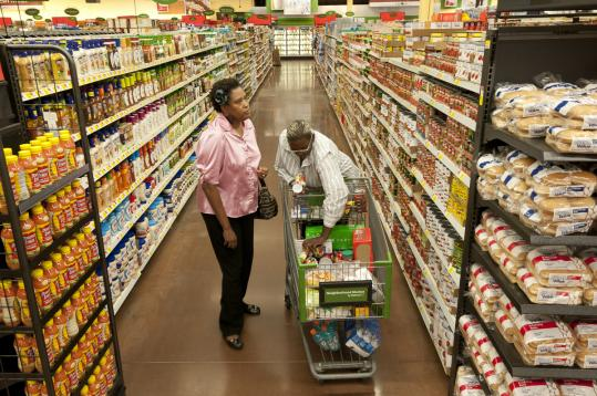 A Walmart market's prices for groceries in Dallas impressed Trena Daffe (left) and her cousin, Lajuanda Bennett.