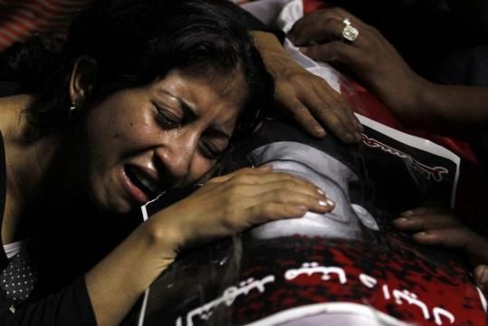 An Egyptian Christian woman mourns on the coffin of Coptic Christian Mina Demian, who was killed during clashes with soldiers Sunday.