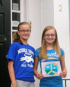 "Madelyn Nelson, 13, of Merrimac (right), created the ""What Peace Means to Me'' button design for the Walk Against Violence and Dorothy's Run 5K on Sunday. She is pictured with her twin sister, Jennifer."