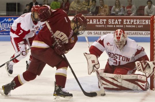 Boston University goalie Kieran Millan makes one of his 35 saves, denying Denver's Jason Zucker near the post during the second period of the Terriers' win.