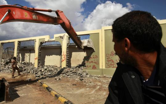 A construction machine demolished the walls of Moammar Khadafy's residence at the Bab al-Aziziyah complex in Tripoli yesterday. The Libyan government plans to put a park there.