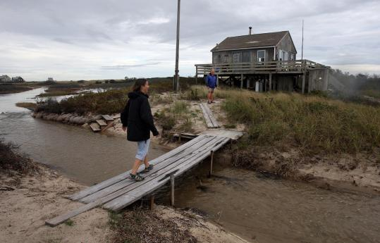 Susan and Roger Carroll at their cottage on North Beach, where several buildings could be swept into the ocean.