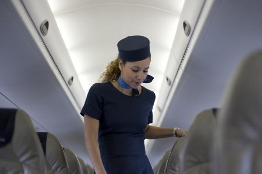 The flight attendants' uniforms, particularly the old-fashioned pillbox hat and scarf, are the signature look of Porter Airlines.