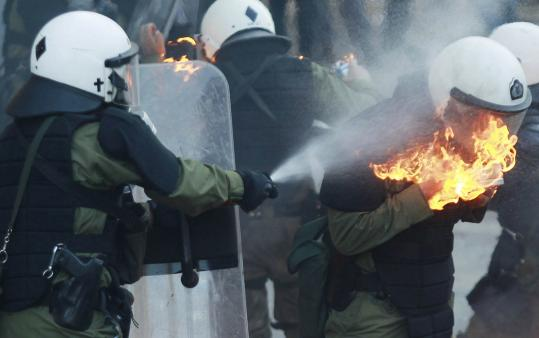 A Greek riot police officer put out the flames when his colleague caught fire from a gas bomb tossed in clashes in Athens. Lawmakers passed a bill yesterday with deep budget cuts.