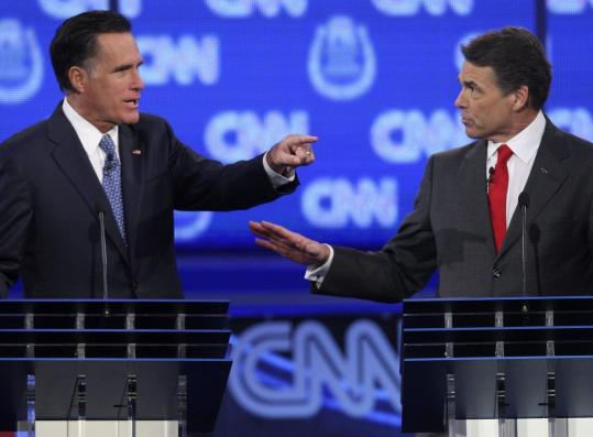 GOP presidential candidates Mitt Romney, left, and Rick Perry debate illegal immigration in Las Vegas Tuesday.