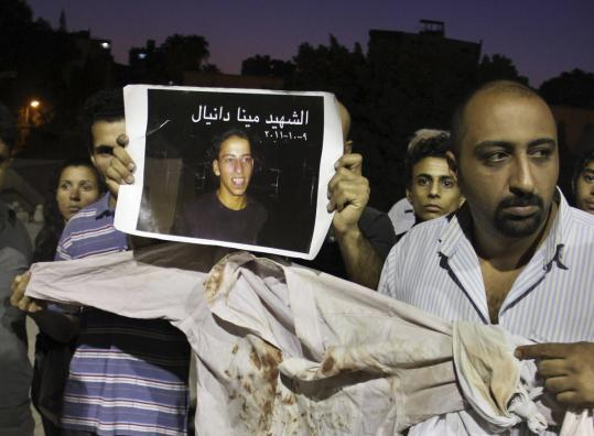 Christians displayed the shirt worn by slain activist Mina Daniel and a picture of him, during a vigil this month outside St. Mark's Cathedral in Cairo for those killed in protests.