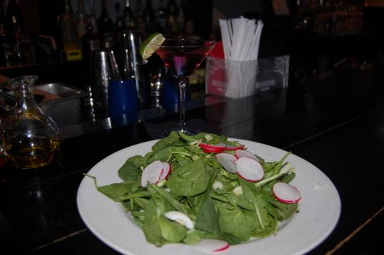 Granite Grill FX gains points for its spinach salad (above), and particularly for its ability to heed a request for special handling, as well as its array of fancy drinks, including an acai-blueberry martini (left) that was featured on the day of a recent visit.