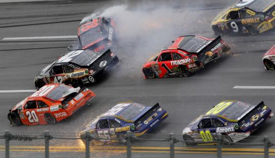 Regan Smith's car (top left) spins out during a crash on Turn 2 with eight laps remaining in the NASCAR Sprint Cup race at Talladega. The accident required repairs to the wall.