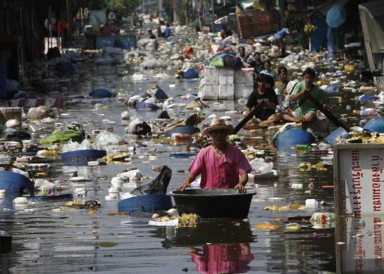Thais pushed their belongings through flood waters during an evacuation from a flooded market in Bangkok yesterday. Workers are trying to bolster levees to protect the city.