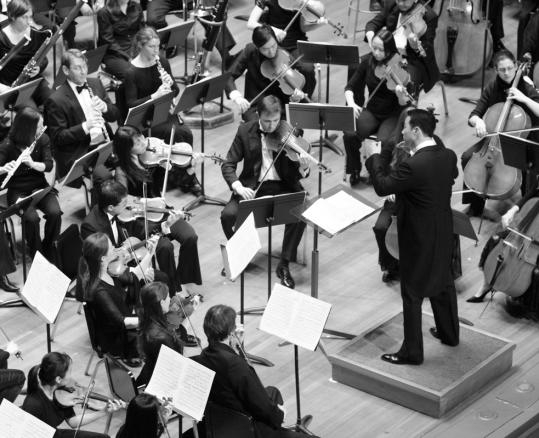 Music director Jin Kim conducting The Atlantic Symphony Orchestra. The musical organization, which serves the South Shore, has a new concertmaster, Ethan Wood (below).