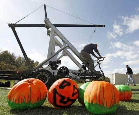 A bicycle-powered catapult helps Chip Hersey launch pumpkins.