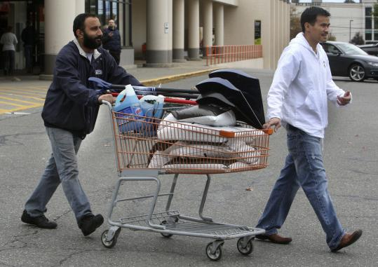 Syed Ovais (left) and Lee Quach bought shovels and ice-melting supplies in Danvers yesterday in anticipation of a snowstorm.