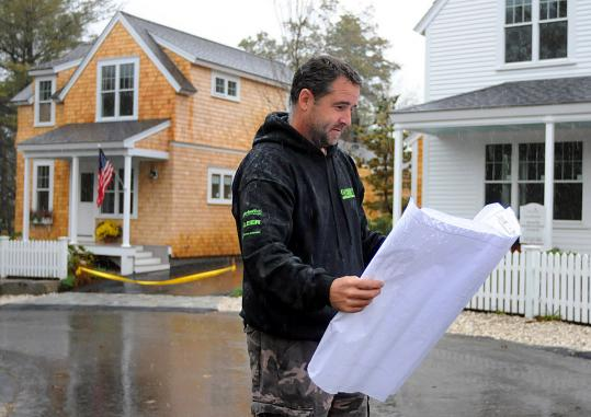 Contractor Bill Wennerberg looked over blueprints near the cottage homes he is building at The Pinehills in Plymouth.