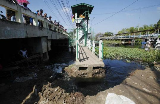 Part of this flood barrier outside Bangkok was destroyed by residents in a bid to move more water from the neighborhood.