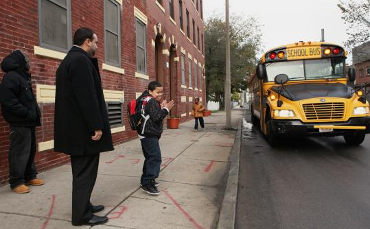 Councilor Felix G. Arroyo and fourth-grader William Candelario waited at the corner of Quincy and Magnolia streets yesterday morning for William's bus. Arroyo and other City Council candidates spent the morning at bus stops to monitor performance.