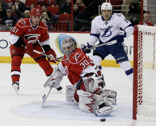 Hurricanes goalie Cam Ward deflects a shot as teammate Tomas Kaberle and Tampa Bay&#8217;s Steve Downie watch.