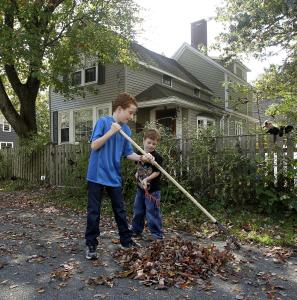 Owen Boesch (left) and his brother Innes rake leaves outside their Hamilton home, which was part of a pilot thermal-imaging program.